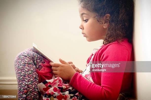 Enfant (5 à 6) lecture sur une tablette graphique numérique à la maison