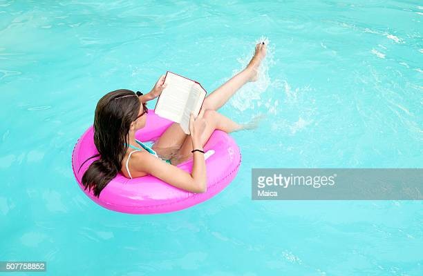 Child reading while floating on a pink lifesaver
