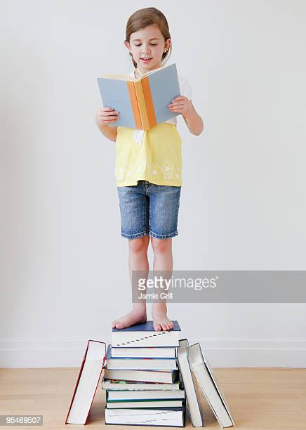 Child reading while standing on books