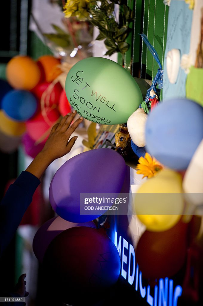 A child reads a get well note on a balloon during a candle lit vigil outside the Mediclinic Heart Hospital in Pretoria where a community group prayed and sang religious songs in support of Nelson Mandela who is receiving treatment there, on June 25, 2013. Mandela's close family gathered today at his rural homestead to discuss the failing health of the South African anti-apartheid icon who was fighting for his life in hospital. Messages of support poured in from around the world for the Nobel Peace Prize winner, who spent 27 years behind bars for his struggle under white minority rule and went on to become South Africa's first black president.