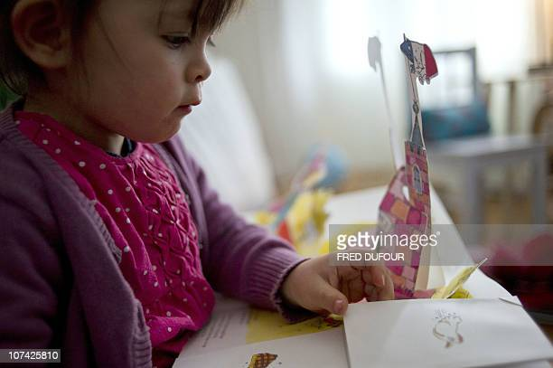 PELLEGRIN A child reads a popup book threedimensional or movable book on December 04 2010 in Paris Popup books made known in the 19th century by...