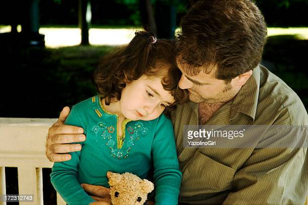 Child receiving comforting hug while holding teddy bear