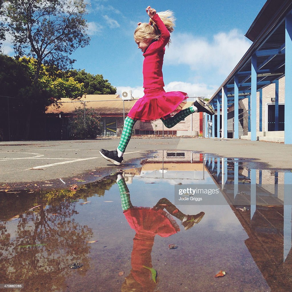 Child reflected in large puddle whilst jumping