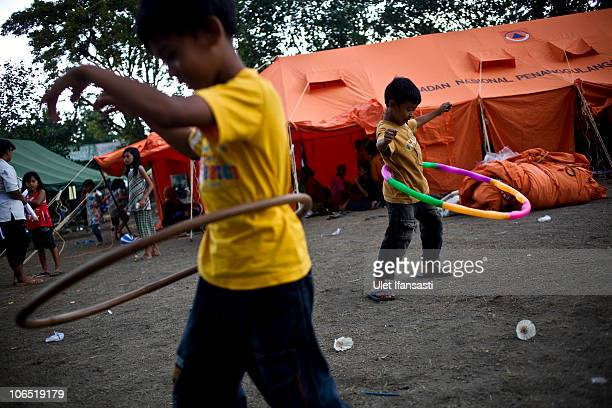 Child refugees play with hula hoops at a temporary evacuation centre set up as a result of the repeated eruptions of Mount Merapi in Keputran village...