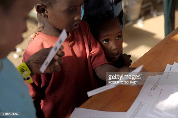 Child refugees receive their vaccination certificates after they were immunized during a medical screening at a registration and food distribution...