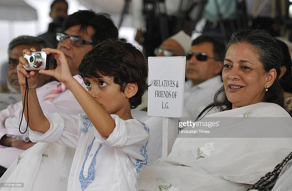 A child relative standing beside Ameena Jung, wife of Newly appointed Lieutenant Governor of Delhi, Najeeb Jung, takes a picture of Najeeb Jung during Jung's swearing in ceremony at Raj Bhawan, on July 9, 2013 in New Delhi, India. 62-year-old Jung has become the 19th Lt Governor of Delhi. A 1973-batch IAS officer, Jung served in Madhya Pradesh government and at several key positions including as joint secretary in the ministry of Petroleum and Natural gas in Central government.