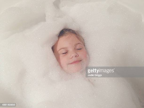 Child relaxing in bathtub full of bubbles