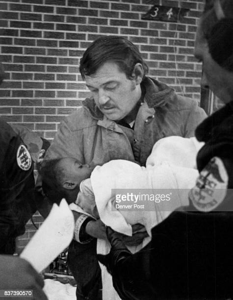 Child Rescued From Burning Home Lt Wayne E Riegel hands Dorothy Bletson of 3240 Madison St to a Denver General Hospital ambulance at tendant after...