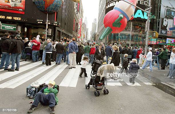 A child rests as a giant balloon passes in Times Square during the 78th Annual Macy's Thanksgiving Day Parade November 25 2004 in New York City...