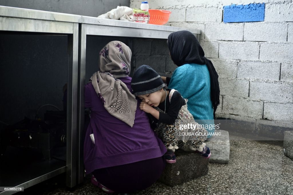 TOPSHOT - A child rests as women prepare food at the Oinofyta refugee camp, some 60 km north of Athens, on March 13, 2017 in Oinofyta. The Oinofyta refugee camp, located some 60km north of Athens, hosts mainly Afghani familes. GOULIAMAKI