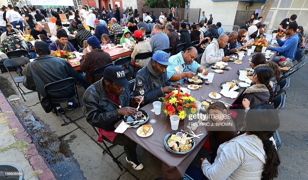 A child rests her head on the table as the homeless and less fortunate enjoy their lunch at the LA Mission's annual Thanksgiving meal in LA's skid row served by celebrities on November 21, 2012 in California. The LA Mission started as a soup kitchen for men of the depression era in 1936 and continues serving meals each day, providing emergency shelter, and helping men and women restore their lives to get back on their feet. AFP PHOTO / Frederic J. BROWN