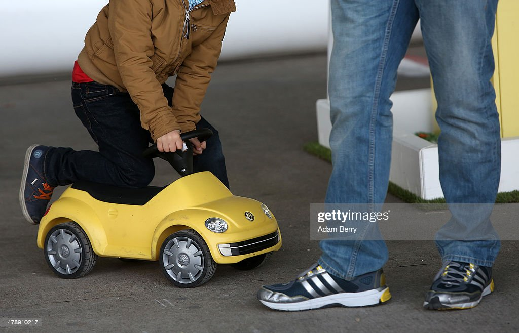 A child rides a toy Volkswagen Beetle at the Electric Mobility Week (e-Mobilitaetswochen), a public Volkswagen (VW) event at the former Tempelhof airport, on March 15, 2014 in Berlin, Germany. The event was designed to promote the company's e-Golf und e-up! automobiles, as well as its other alternative energy powered vehicles.