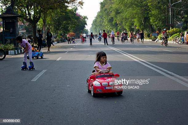 A child rides an electric toy car in Solo city's main avenue on June 15 2014 during the carfree Sunday morning in the central Java island city...