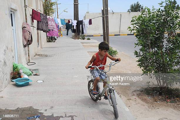 A child rides his bicycle in his neighborhood named 'Arab Quarters' on April 15 2012 in Kish Iran Kish is a 915squarekilometre resort island in the...