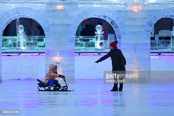 A child rides on a sleigh past snow sculptures during the Harbin International Ice and Snow Festival in Harbin northeast China's Heilongjiang...