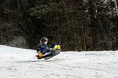 Winter snow activity. A child riding a sledge downhill and jump in mid air.
