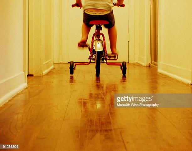 Child riding bike with training wheels in hallway