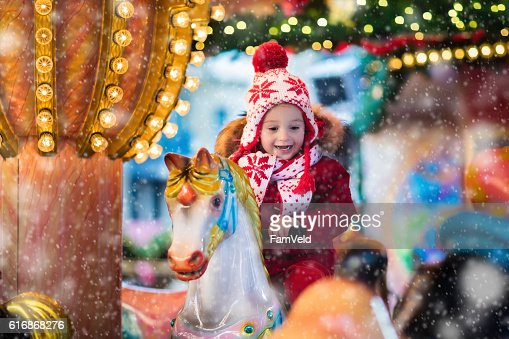 Child riding carousel on Christmas market : Stock Photo