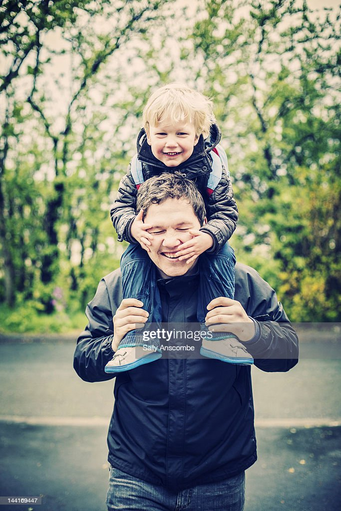 Child riding on his fathers shoulders : Stock Photo