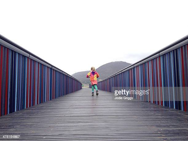 Child riding scooter along wooden walkway