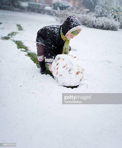 Kind Rolling Snowball für Schneemann im Freien