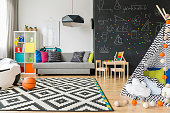 Spacious black and white child room with window, sack chair, regale, sofa, carpet, chalkboard wall, small table, chairs and play tent