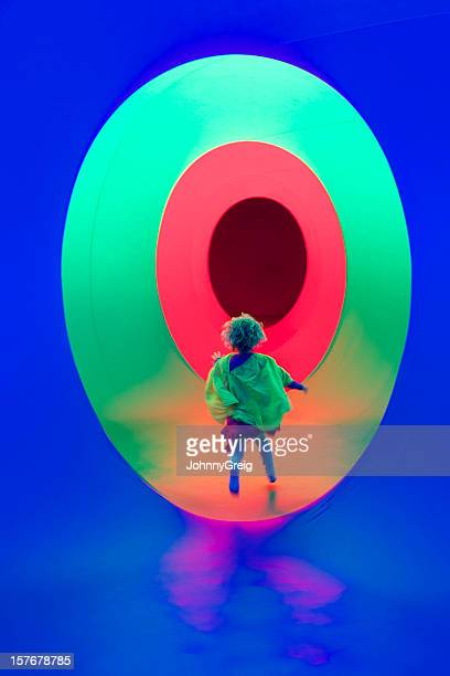 Child running in a colourful tunnel