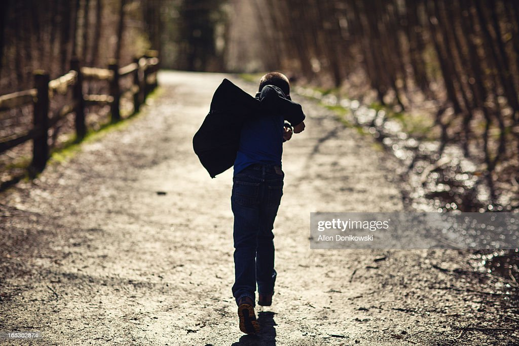 child running into forest on trail : Stock Photo