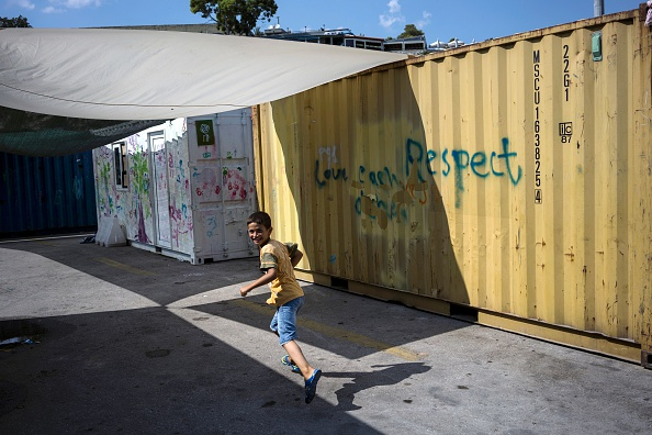 A child runs among containers at the port of Piraeus, where nearly 1,500 refugees and migrants live at a makeshift camp or in passenger areas, in Athens on July 3, 2016