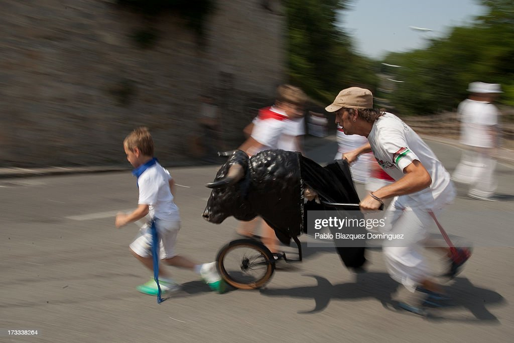 A child runs in front of a toy bull during the Encierro Txiki (Little Bull Run) on the seventh day of the San Fermin Running Of The Bulls festival on July 12, 2013 in Pamplona, Spain. The annual Fiesta de San Fermin, made famous by the 1926 novel of US writer Ernest Hemmingway 'The Sun Also Rises', involves the running of the bulls through the historic heart of Pamplona, this year for nine days from July 6-14.