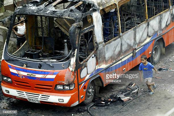 A child runs next to a burnt down bus 26 April in Cali Valle del Cauca department Colombia Colombian President Alvaro Uribe has temporarily installed...