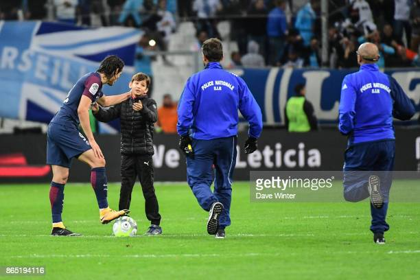 A child runs onto the pitch to ask Edinson Cavani of PSG for his shirt during the Ligue 1 match between Olympique Marseille and Paris Saint Germain...