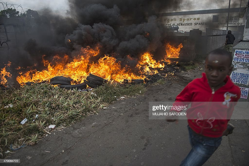 A child runs pass burning tires during the xenophobic violence on 17 April 2015 in Jeppestown area of central Johannesburg Twelve people were...