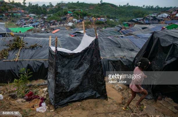 COX'S BAZAR BANGLADESH SEPTEMBER 19 A child runs past a makeshift toilet in the Falungkhali Rohingya refugee camp on September 19 2017 in Cox's Bazar...