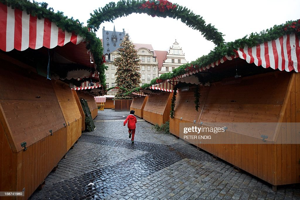 A child runs past closed stands at the Christmas market in Leipzig, eastern Germany, on December 27, 2012.