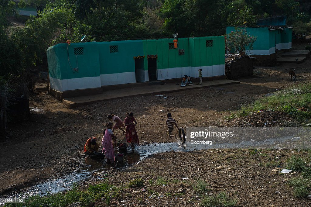 A child runs past while women wash their clothes at a stream in Bhilkhera village, Maharashtra, India, on Thursday, Nov. 15, 2012. The Indian economy will expand 4.9 percent in 2012, the least in a decade, according to the International Monetary Fund. Photographer: Sanjit Das/Bloomberg via Getty Images