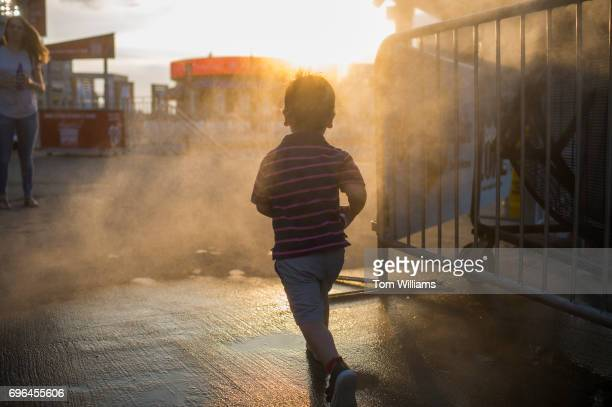 A child runs through a cool zone during the 56th Congressional Baseball Game at Nationals Park on June 15 2017