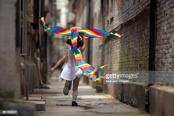 A child runs with a kite.