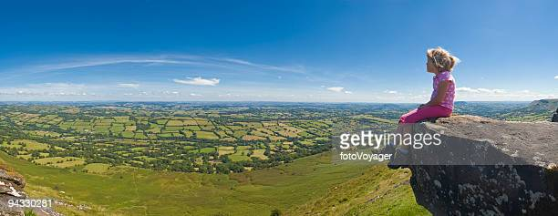 Child sat on mountain looking over panoramic view to blue