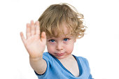 Child saying no. Toddler lifting hand in protest isolated on white background.