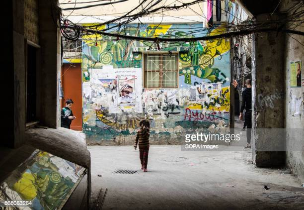 A child seen walking towards the camera beyond her a coloured graffiti on the wall above her electric wires and water tubes are running as a spider's...