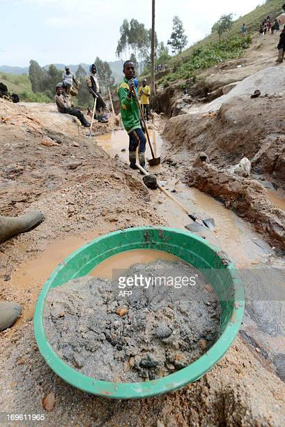 A child separates mineral from rock and sand on May 28 2013 near the Mudere mine outside Rubaya some 9 kms from the eastern Democratic Republic of...