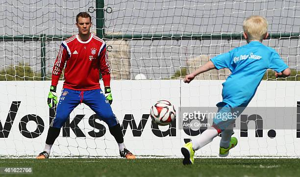 A child shoots a penalty against goalkeeper Manuel Neuer during day 8 of the Bayern Muenchen training camp at ASPIRE Academy for Sports Excellence on...