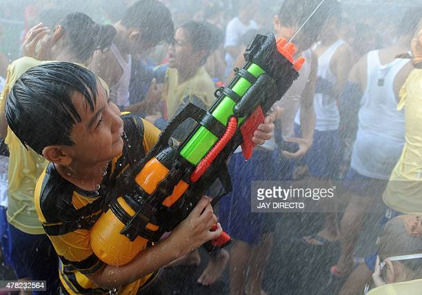 A child shoots a watergun as revellers celebrate the feast day of St John the Baptist in Manila on June 24 2015 Philippine residents celebrate the...