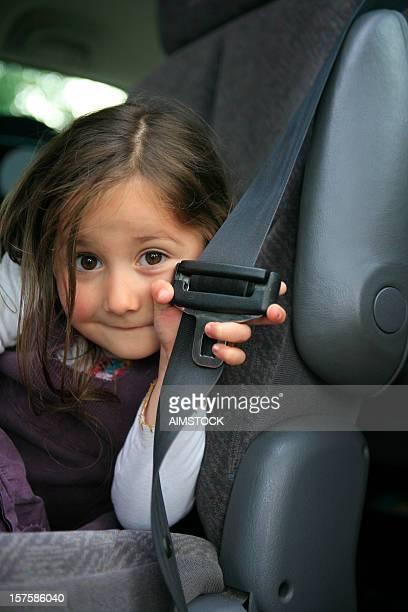 Niño, mostrando cinturón de seguridad de coche