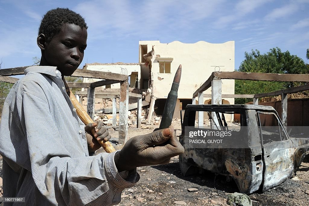 A child shows a heavy machine gun bullet on February 5, 2013 that he found in the ruins of a building destroyed by French air strikes in Douentza.The town was retaken by French and Malian troops in January. AFP PHOTO / PASCAL GUYOT