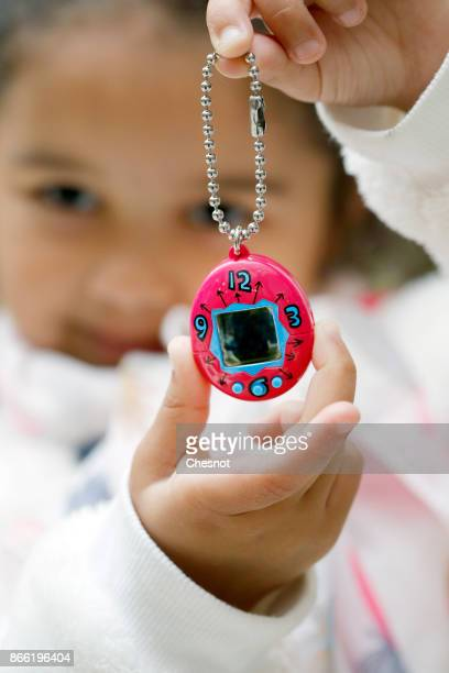 A child shows a 'Tamagotchi' electronic pet toy on October 25 2017 in Paris France Tamagotchi is a virtual electronic animal which means 'cute little...