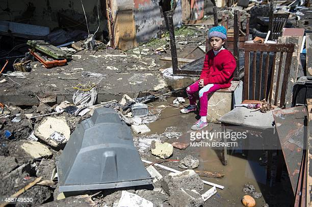 A child sits amid debris caused by the sea in Coquimbo some 445 km north of Santiago during the eve's earthquake on September 17 2015 A million...