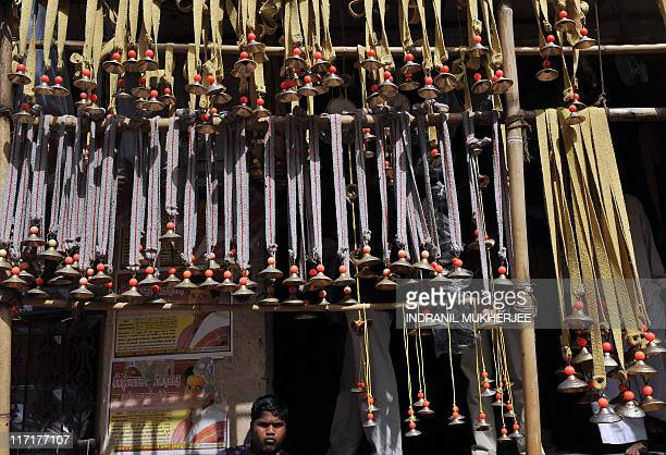 A child sits at his family owned shop selling bells near the temple of Saint Dnyaneshwar during the annual pilgrimage of VarkariHindus at Alandi some...