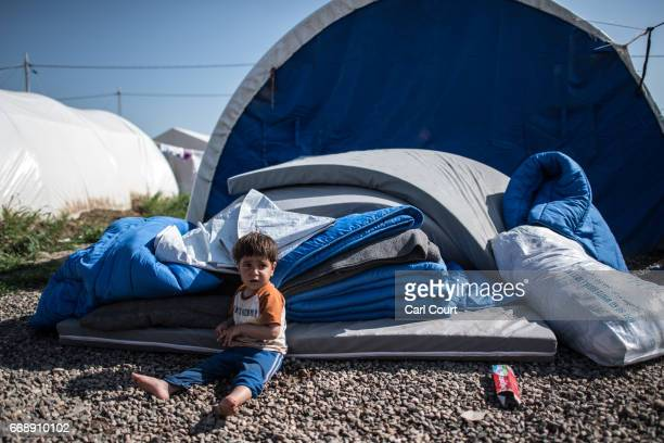 A child sits by bedding supplied to new arrivals in Khazir refugee camp on April 15 2017 near Mosul Iraq Khazir camp with a capacity of roughly 30000...